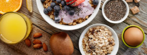 Granola and yogurt with fruit, juice, and eggs